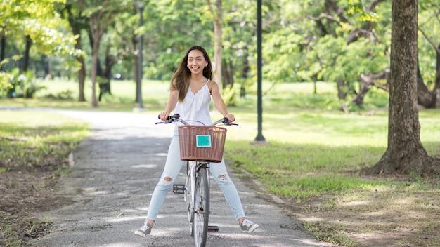 여름에 햇빛과 단풍 bokeh 배경으로 공원에서 자전거를 타고 아시아 아름 다운 행복 한 젊은 여자 다리. 사람들이 건강하고 스포츠 라이프 스타일 개념.