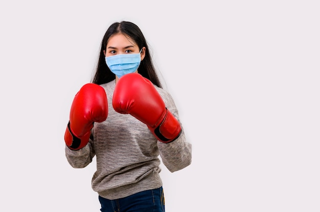Asian beautiful happy young woman wearing mask protection and boxing gloves her get ready for coronavirus fighting against, with copy space