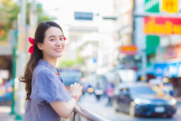 Азиатская красивая дама в голубо-сером платье ципао стоит, счастливо улыбаясь, придорожный китай-таун