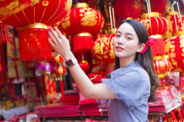 Азиатская красивая дама с длинными волосами носит серое китайское платье или ципао с китайской новогодней тематикой.