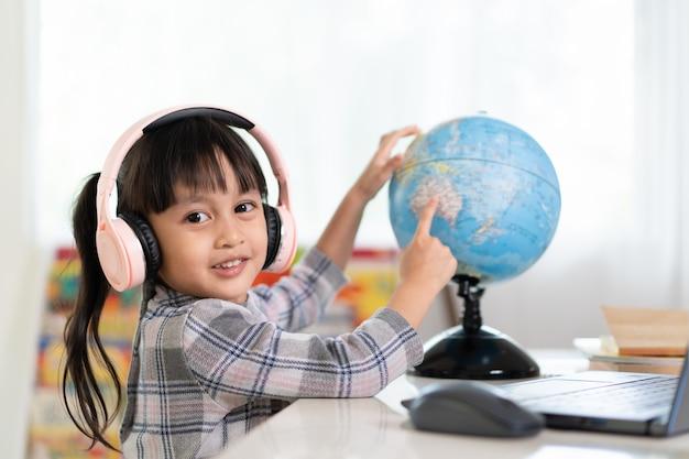 Азиатская красивая маленькая девушка студента усмехающся и указывающ на двуязычную модель глобуса для ее онлайн урока.