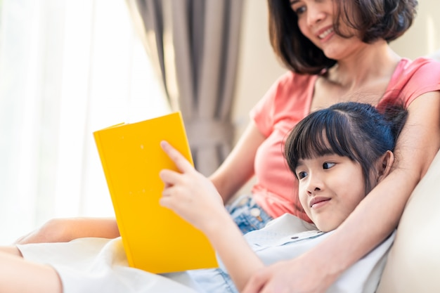 Asian beautiful mother and her daughter reading fairytail story book on sofa at home together.