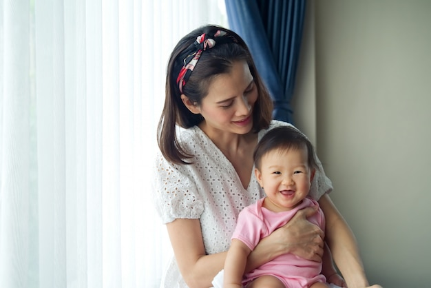 Asian beautiful mother holding her cute baby in her arms sitting near the window.