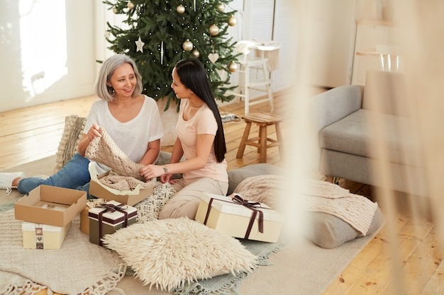 Asian beautiful mother opening christmas presents together with her daughter on the floor in the room
