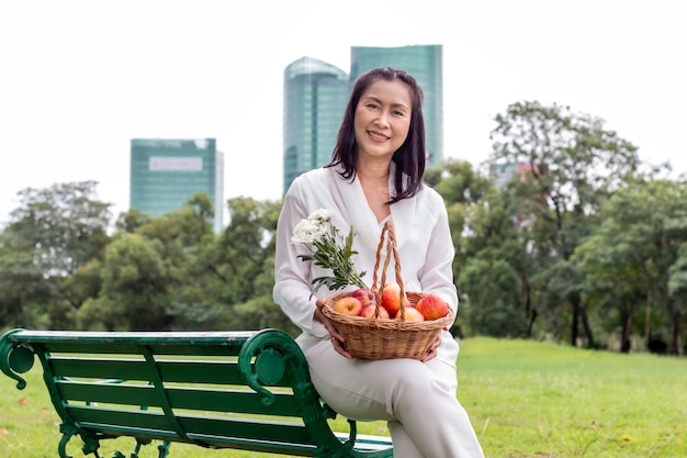 Asian beautiful portrait of senior woman with fruit basket and flower in the park.