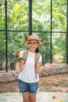 Asian beautiful small cute child enjoying with love bird on hand