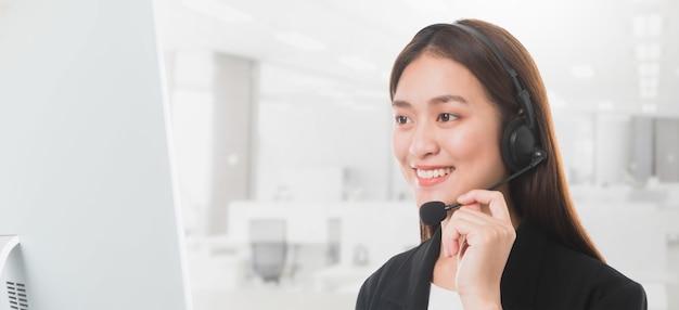 アジアの美しい笑顔の女性の顧客サポート電話オペレータのオフィススペースの背景。