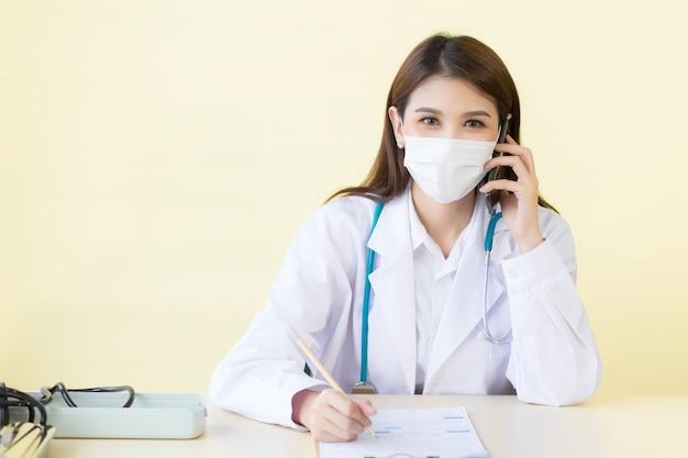 아시아의 아름다운 여성 의사는 직장에서 환자의 증상을 확인하기 위해 전화를 걸고 글을 씁니다.