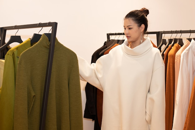 Asian beautiful woman in dress select new collection on white orange green earth tone clothes rack in retail fashion store which just open brand news for winter autumn as minimal style