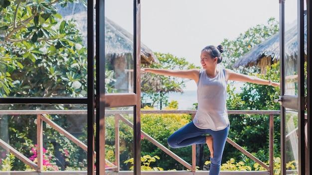 Азиатская красивая женщина занимается спортом и занимается йогой дома. концепция физических упражнений во время карантина дома для предотвращения заражения коронавирусом и covid-19.