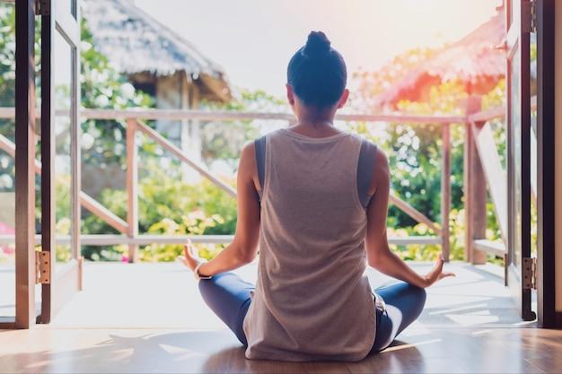 Азиатская красивая женщина тренируется и играет в йогу дома.