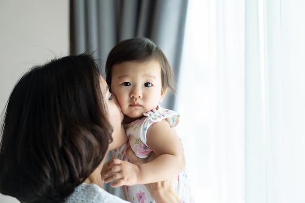 Азиатская красивая женщина держа младенца и целуя щеку ребенк в комнате дома.