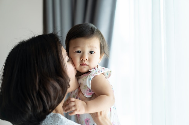 Asian beautiful woman holding baby and kissing the kid cheek in room at home.