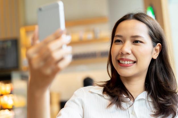 スマートフォンを保持し、selfieスナップショットまたはライブビデオのフロントカメラを使用してアジアの美しい女性