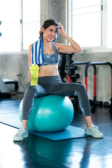 Asian beautiful woman holding water bottle and sitting on fit ball after exercise in fitness gym
