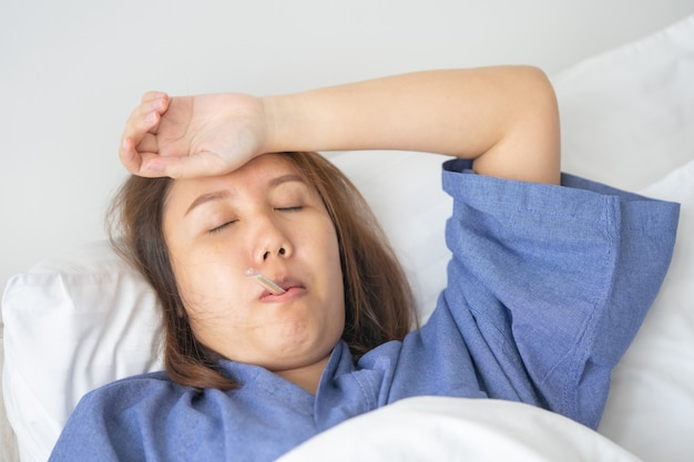 Asian beautiful woman hypothermia has been measured by fever. lie on the bed