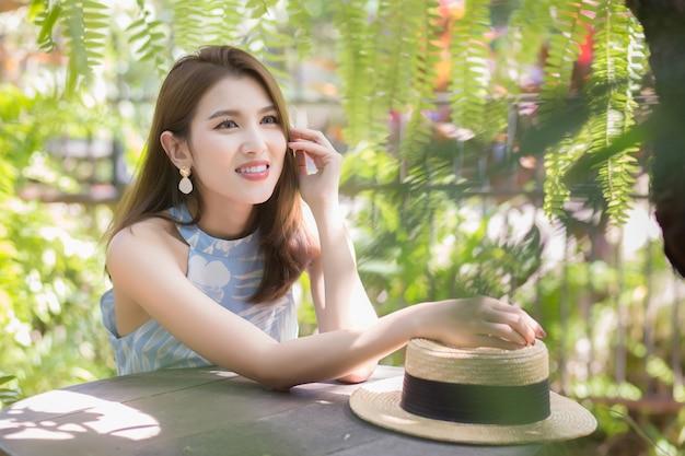 青いドレスを着たアジアの美しい女性は、良い気分で長い散歩の後に休んでいます、幸せは屋外の庭にいる間木々を見ました。