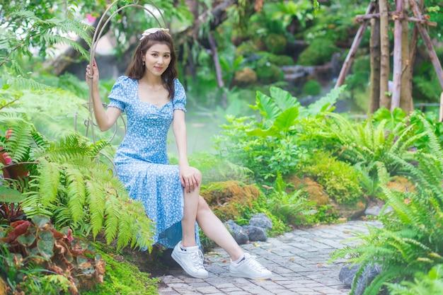 파란 드레스를 입은 아시아 아름다운 여성이 녹색 정원 배경에 행복하게 웃고 있습니다.