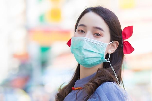 치파오 드레스를 입은 아시아의 아름다운 여성이 마스크를 쓰고 행복하게 웃는 얼굴로 서 있다