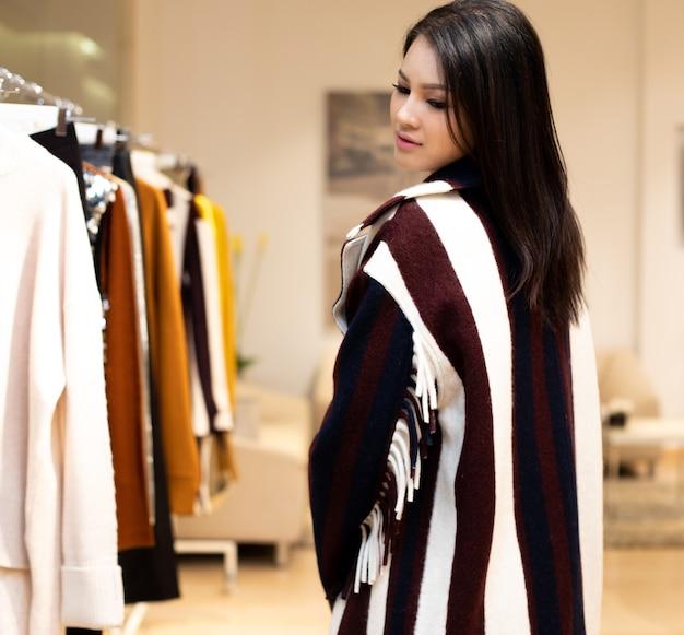黒と白のドレスを着たアジアの美しい女性は、カジュアルなスタイルとして冬の秋のブランドニュースを開くだけの小売ファッション店の既製服ラックの新しいコレクションを選択します