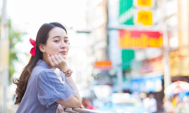 Азиатская красивая женщина в голубо-сером платье ципао стоит счастливым улыбающимся придорожным китай-таун
