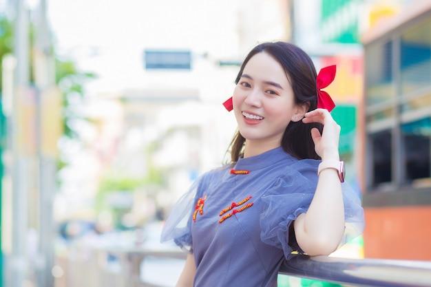 Азиатская красивая женщина в голубо-сером платье ципао стоит, счастливо улыбаясь, придорожный китай-город