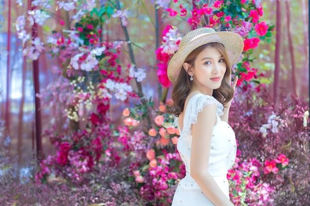色とりどりの花の間に立っている間、茶色の髪のアジアの美しい女性は白いドレスと帽子をかぶっています