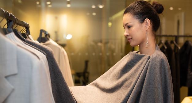 ドレスを着たアジアの美しい女性は、最小限のスタイルとして冬の秋のブランドニュースを開くだけの小売ファッション店のグレーアースカラーのハンガーラックで新しいコレクションを選択します