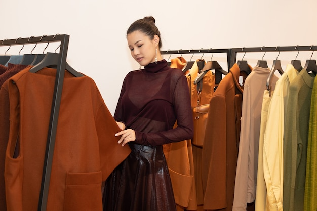 ドレスを着たアジアの美しい女性は、最小限のスタイルとして冬の秋のブランドニュースを開くだけの小売ファッション店のオレンジグリーンアーストーンの洋服ラックで新しいコレクションを選択します