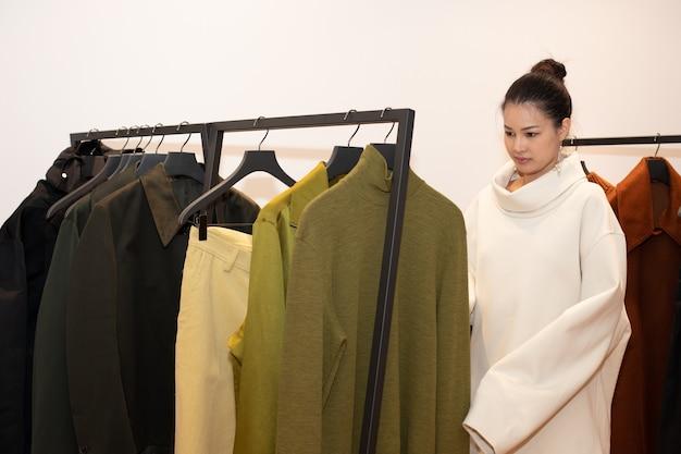 ドレスを着たアジアの美しい女性は、ミニマルスタイルとして冬の秋のブランドニュースを開くだけの小売ファッション店のホワイトオレンジグリーンアーストーンの洋服ラックで新しいコレクションを選択します