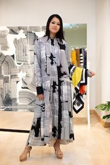 グラフィックドレスを着たアジアの美しい女性は、カジュアルなスタイルとして冬の秋のブランドニュースを開くだけの小売ファッション店の既製服ラックの新しいコレクションを選択します