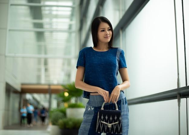 インディゴブルーの地元の綿のドレスのアジアの美しい女性は、大きな窓とコピースペースのテキストロゴの背景をぼかすファッションストアで既製服の新しいコレクションを提示します