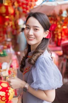 Азиатская красивая женщина с длинными волосами носит серое китайское платье или ципао с темой китайского нового года.
