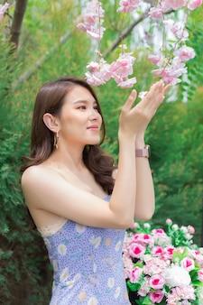 紫色のドレスを着たアジアの美しい女性は、彼女が幸せに微笑む庭の花で賞賛します