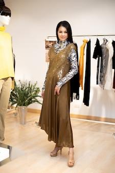 シルバーのスパンコールドレスを着たアジアの美しい女性が、カジュアルなスタイルとして冬の秋のブランドニュースを開くばかりの小売ファッションストアの既製服ラックで新しいコレクションを選択します