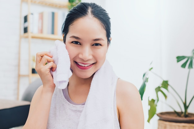 Asian beautiful woman resting and holding towel after play yoga and exercise at home
