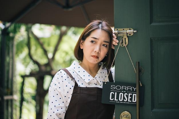 바이러스 감염으로 인해 카페 문에 매달려 닫힌 사인 보드와 함께 아시아 아름다운 여자 슬픈 분위기