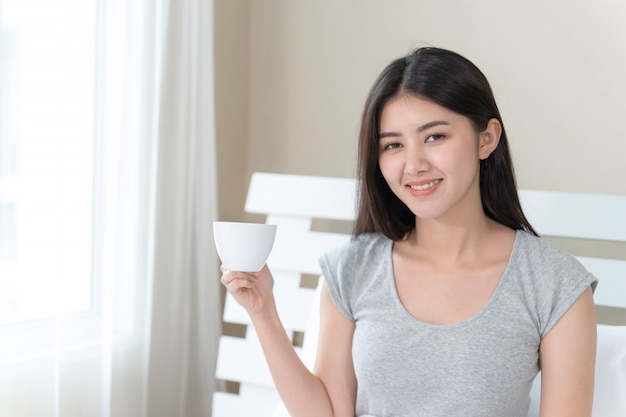 Asian beautiful woman sitting on bed in the bedroom and holding coffee cup in hand with happy