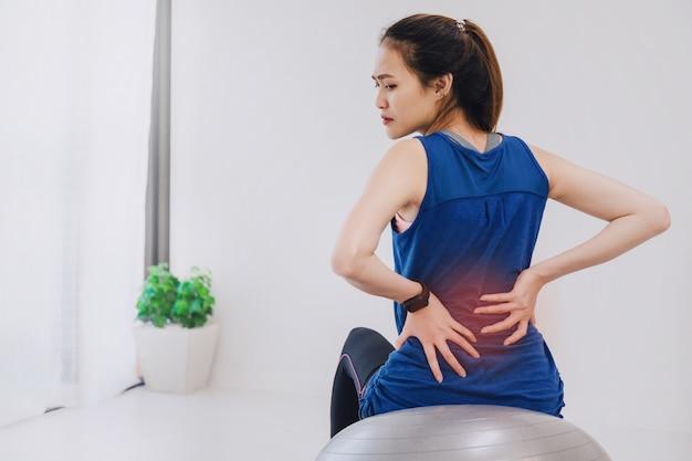 フィットボールの上に座って、ヨガをし、自宅で運動しながら腰痛を感じるアジアの美しい女性。