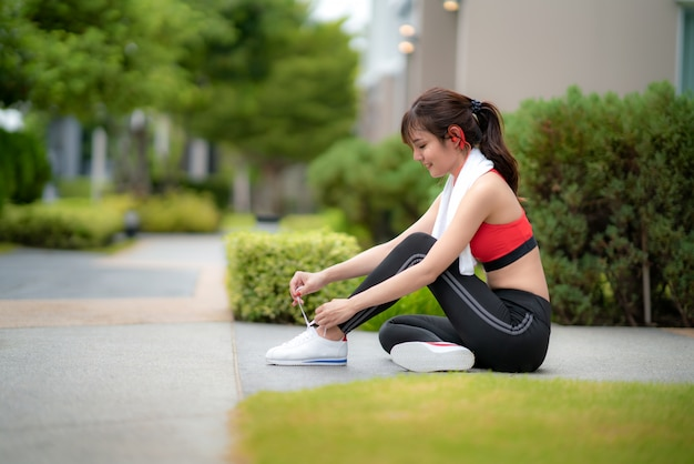 Asian beautiful woman sitting for relax and trying shoelaces in font of her house in village, happy and smile in morning during sunlight. sport fitness model asian ethnicity training outdoor concept.