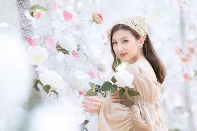아시아의 아름다운 여성은 자연스럽고 고급스러운 테마로 하얀 장미 꽃 정원에 서서 미소를 짓고 있습니다.