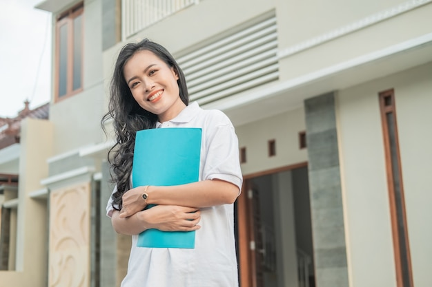 Asian beautiful woman standing holding home certificate in front of a new home