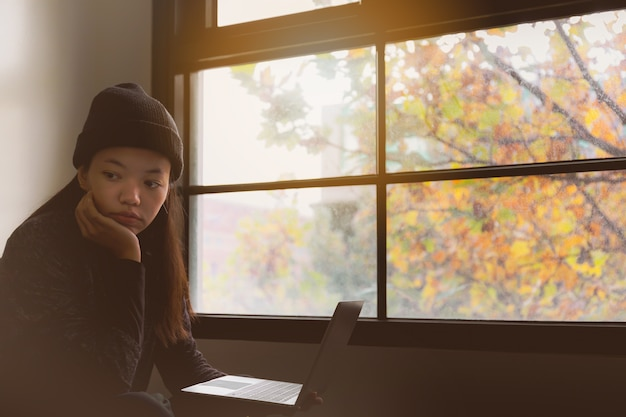Asian beautiful woman student thinking and working with laptop in room.