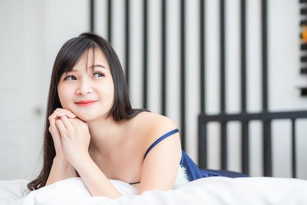 아시아의 아름다운 여인, 태국인 그녀는 연인에 대해 생각하고 잠옷을 입고 침대에 누워있는 것처럼 웃고있었습니다.