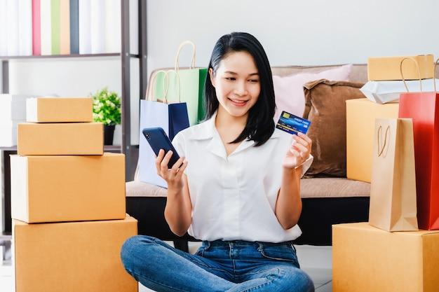 自宅でオンラインショッピングのクレジットカードでスマートフォンを使用してアジアの美しい女性