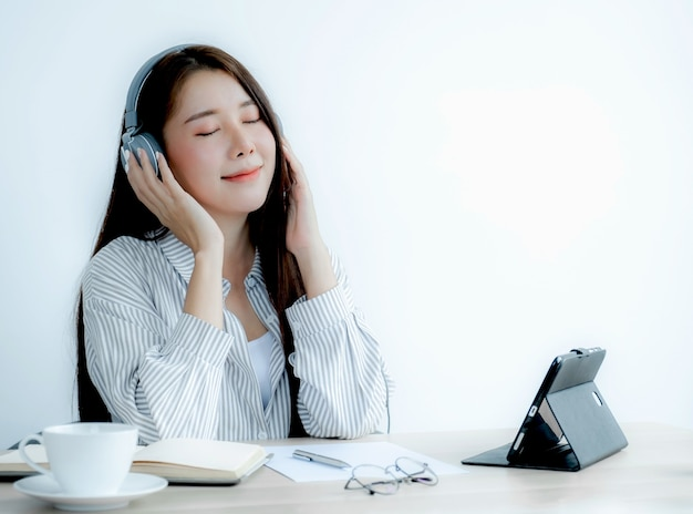 Азиатская красивая женщина в наушниках слушайте музыку онлайн через планшет, расслабляясь в домашнем офисе перед работой.