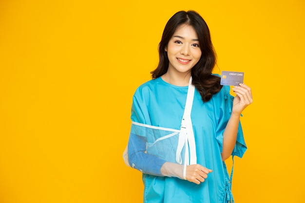 Asian beautiful woman wearing patient holding credit card isolated on yellow wall.