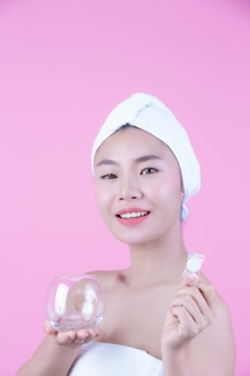 Asian beautiful woman wiping the face on a pink background, cosmetology and spa .