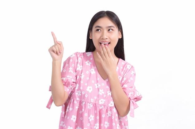 ピンクのシャツに黒い長い髪のアジアの美しい女性は、何かを提示するために手を指します