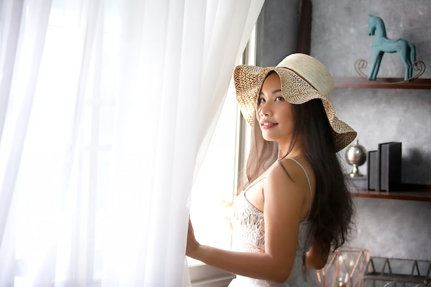 Asian beautiful woman with a hat fashion posing indoors by window in warm glow of the sun